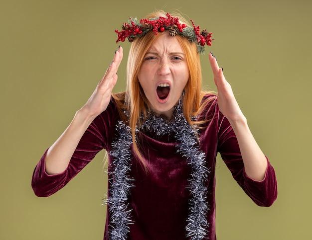 Giovane bella ragazza arrabbiata che porta vestito rosso con la corona e la ghirlanda sul collo isolato su priorità bassa verde oliva