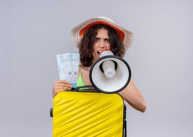 Сердитая молодая красивая женщина путешественника в шляпе и держит билеты на самолет и чемодан и разговаривает спикером на изолированной белой стене