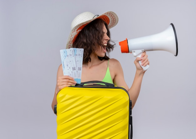 Angry young beautiful traveler woman wearing hat and holding airplane tickets and suitcase and talking by speaker on isolated white wall