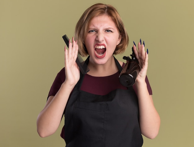 Angry young beautiful woman hairdresser in apron holding hair clip spray bottle and comb shouting going wild standing over green wall