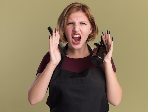 Сердитая молодая красивая женщина-парикмахер в фартуке держит бутылку со спреем для заколки и расческу, крича, сходит с ума, стоя над зеленой стеной