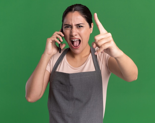Сердитая молодая красивая женщина-парикмахер в фартуке разговаривает по мобильному телефону, кричит с агрессивным выражением лица, показывая указательный палец, стоящий над зеленой стеной