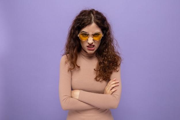腕を組んで眉をひそめている顔で見て黄色いメガネをかけているベージュのタートルネックの怒っている若い美しい女性