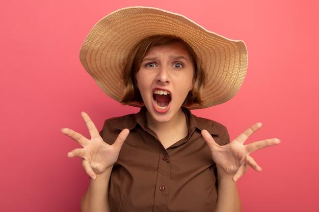 Giovane ragazza bionda arrabbiata che indossa cappello da spiaggia che guarda mostrando le mani vuote isolate sul muro