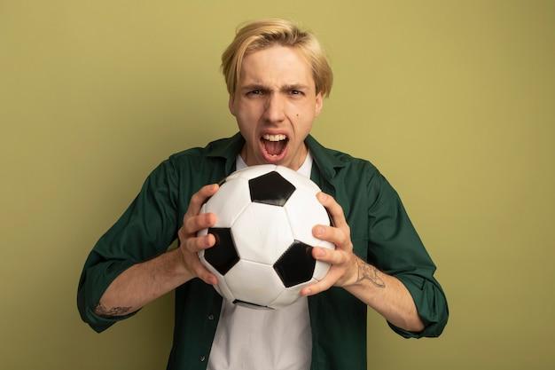 Злой молодой блондин в зеленой футболке держит мяч