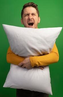 緑の壁に孤立してまっすぐに見て叫んで枕を抱き締めて怒っている若いブロンドのハンサムな男