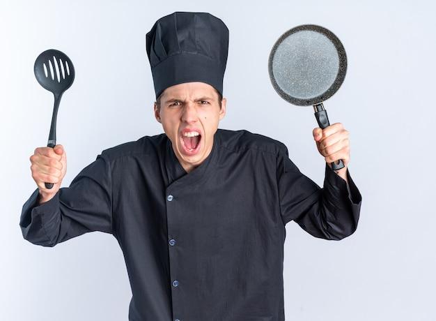 Giovane cuoco maschio biondo arrabbiato in uniforme da chef e berretto che guarda l'obbiettivo che mostra spatola e padella urlando isolato sul muro bianco