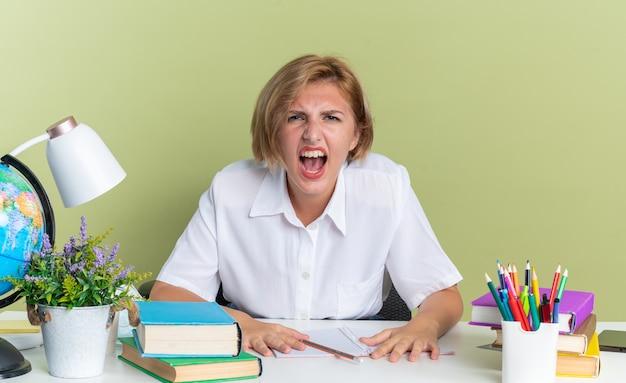机の上で叫びながら学校の道具を持って机に座っている怒っている若いブロンドの学生の女の子