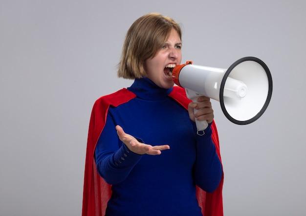 Giovane ragazza bionda arrabbiata del supereroe in mantello rosso che grida in altoparlante guardando dritto mostrando la mano vuota isolata sul muro bianco con lo spazio della copia