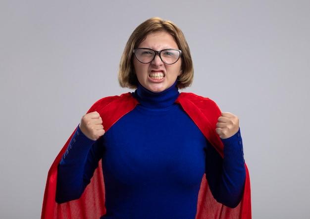 Arrabbiato giovane donna bionda supereroe in mantello rosso con gli occhiali guardando i pugni di serraggio anteriori isolati sul muro bianco
