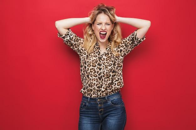 Сердитая молодая блондинка в макияже кричит изолированно на красном фоне
