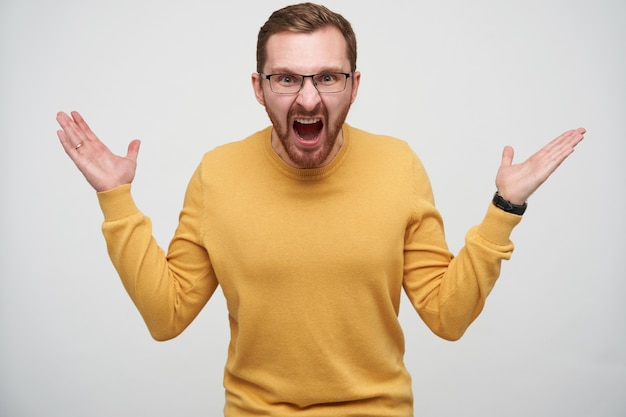 Angry young brown haired bearded man in glasses raising emotionally palms up and shouting heatedly, standing