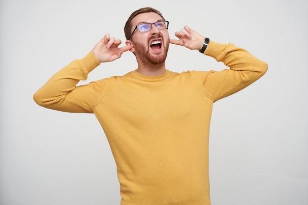 Злой молодой брюнет бородатый самец засовывает в уши указательные пальцы и яростно смотрит вверх, пытаясь избежать раздражающих звуков, позирует в повседневном свитере