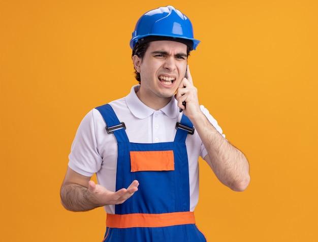 オレンジ色の壁の上に立っている携帯電話で話している建設制服と安全ヘルメットの怒っている若いビルダーの男