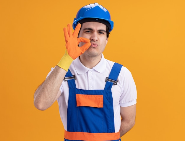 オレンジ色の壁の上に立っているジッパーで口を閉じるような沈黙のジェスチャーをするゴム手袋を身に着けている建設制服と安全ヘルメットの怒っている若いビルダーの男