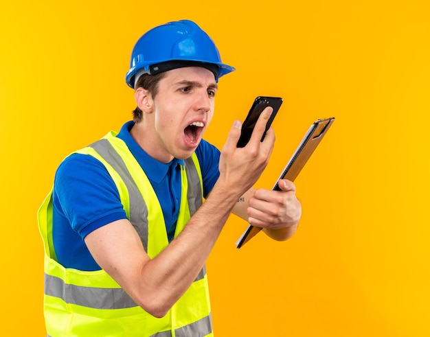 클립보드를 들고 손에 전화를 보고 있는 제복을 입은 화난 젊은 건축업자