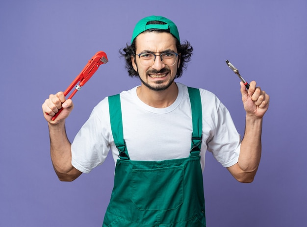 Angry young builder man wearing uniform with cap holding roller brush with open-end wrench