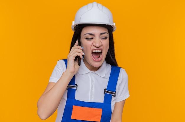 Giovane donna arrabbiata del costruttore in uniforme da costruzione e casco di sicurezza che grida impazzendo mentre parla al telefono cellulare in piedi sopra la parete arancione