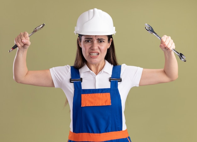 オリーブグリーンの壁に分離されたオープンエンドのレンチを上げる制服を着た怒っている若いビルダーの女性