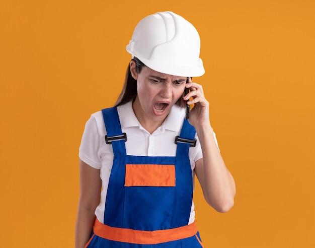 La giovane donna arrabbiata del costruttore in uniforme parla sul telefono isolato sulla parete arancione