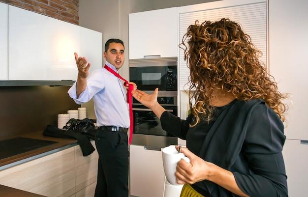 넥타이를 매는 동안 집에서 곱슬머리 여자와 말다툼을 하는 화난 젊은 사업가
