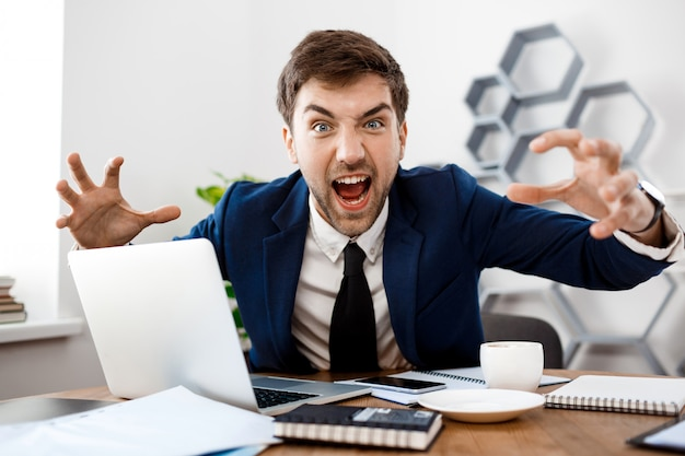 Angry young businessman shouting, office background.