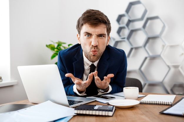 Angry young businessman sitting at workplace, office background.