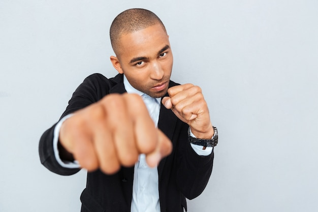 Angry young businessman standing in boxer position and ready to fight