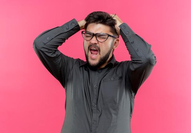 眼鏡をかけている怒っている青年実業家はピンクで隔離の頭をつかんだ