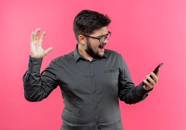 Сердитый молодой бизнесмен в очках держит и смотрит на телефон и поднимает руку, изолированную на розовой стене