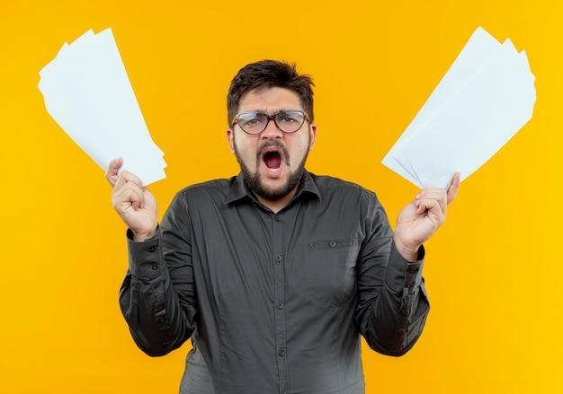 Сердитый молодой бизнесмен в очках, поднимающий документы, изолированные на желтом