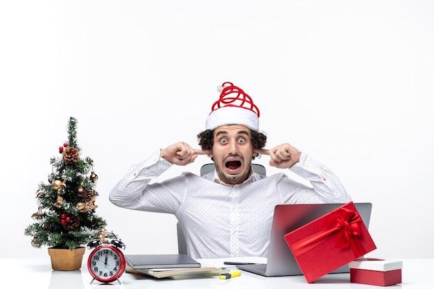 Сердитый молодой бизнесмен с забавной шляпой санта-клауса празднует рождество, закрывая уши, мешает слушать в офисе на белом фоне