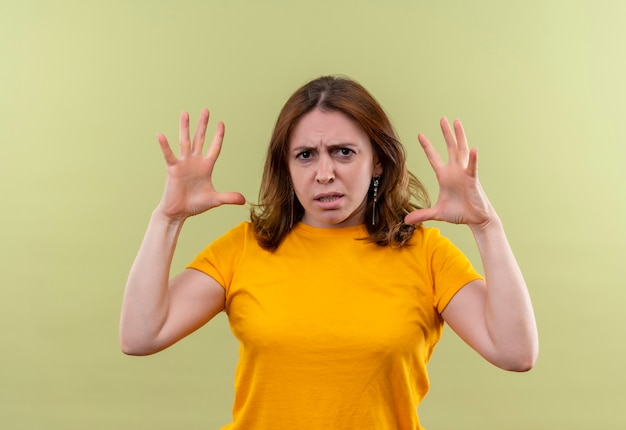 Angry young casual woman with raised hands on isolated green space