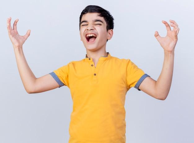 Сердитый молодой кавказский мальчик держит руки в воздухе с закрытыми глазами, изолированными на белом фоне