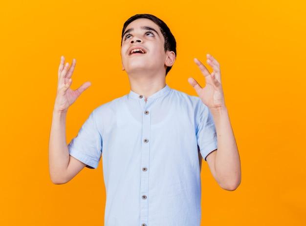 Злой молодой кавказский мальчик смотрит вверх, держа руки в воздухе, изолированные на оранжевом фоне