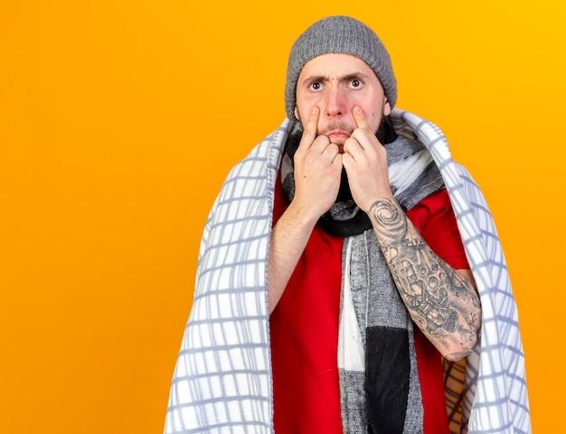 격자 무늬에 싸여 겨울 모자와 스카프를 착용하는 화가 젊은 백인 아픈 남자가 복사 공간이 오렌지 벽에 고립 된 눈꺼풀을 당깁니다