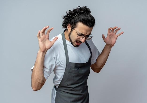 Злой молодой кавказский мужчина-парикмахер в очках и волнистой повязке для волос в униформе, поднимая руки с закрытыми глазами, изолированными на белом фоне