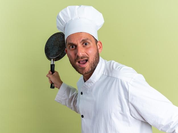 Сердитый молодой кавказский мужчина-повар в униформе шеф-повара и кепке стоит в профиль, держа сковороду