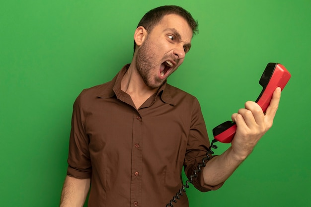Angry young caucasian man holding old telephone looking at it screaming isolated on green wall