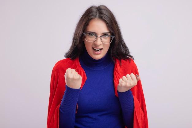 白い壁に分離された拳を握りしめ眼鏡をかけている赤いマントの怒っている若い白人のスーパーヒーローの女の子