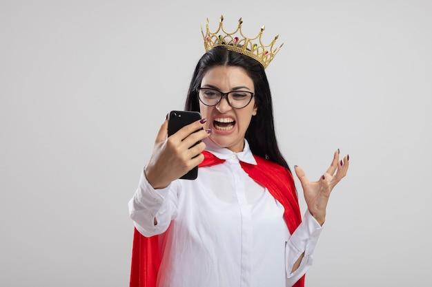 안경과 왕관을 착용하고 복사 공간이 흰색 배경에 고립 된 공기에 손을 유지하는 휴대 전화를보고 화가 젊은 백인 슈퍼 히어로 소녀