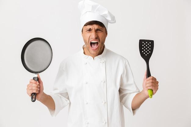 Сердитый молодой шеф-повар стоит изолированно на белой стене, держа сковороду