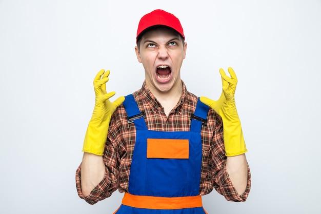 制服と手袋のキャップを身に着けている怒っている若い掃除人