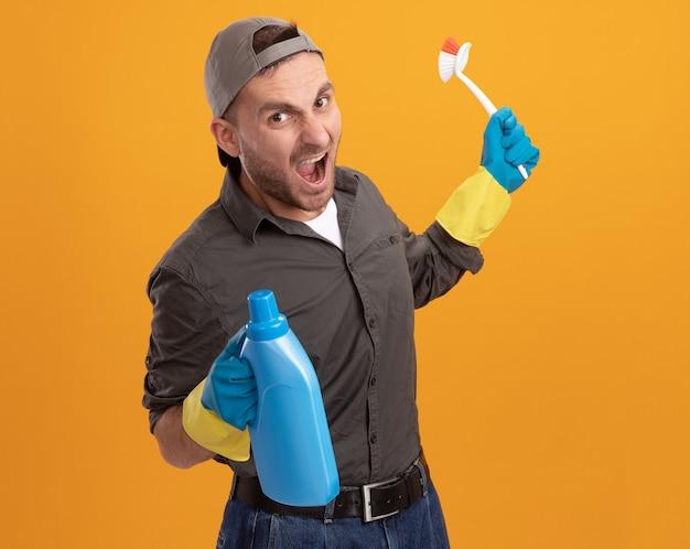 オレンジ色の壁の上に立っている積極的な表情で叫んでいるクリーニング用品とクリーニングブラシとボトルを保持しているゴム手袋でカジュアルな服とキャップを身に着けている怒っている若いクリーニング男