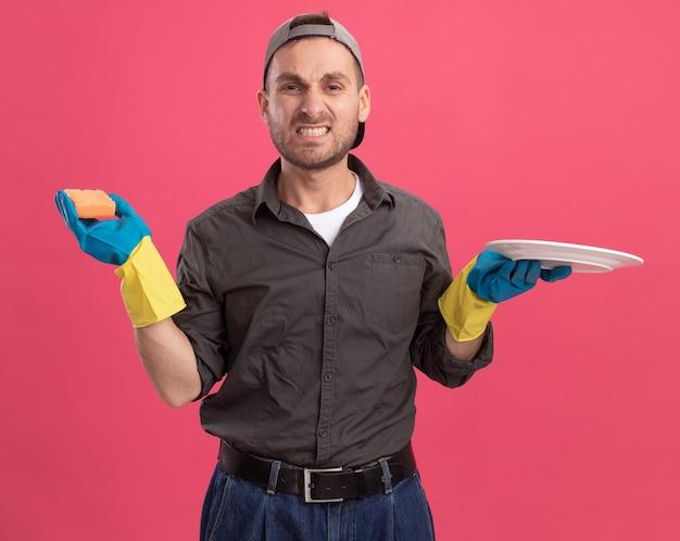 Arrabbiato giovane uomo delle pulizie che indossa abiti casual e berretto in guanti di gomma tenendo piatto e spugna con espressione infastidita in piedi sopra la parete rosa