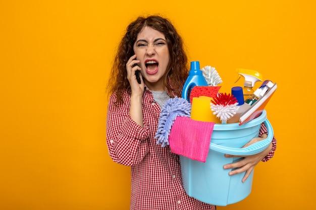 Giovane donna delle pulizie arrabbiata che tiene secchio di strumenti per la pulizia e parla al telefono