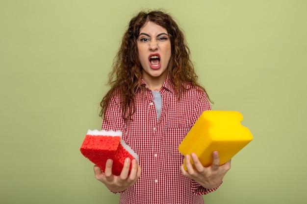 クリーニングスポンジを保持している怒っている若いクリーニング女性
