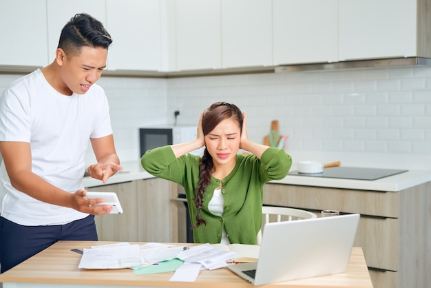 Angry young couple arguing by their many debts at home