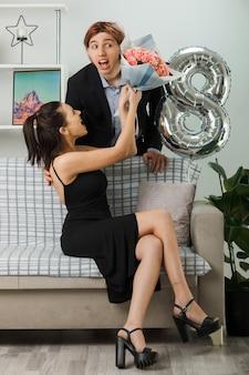 Сердитая молодая пара на счастливом женском дне, парень, стоящий за диваном, девушка, сидящая на диване, держа букет в гостиной