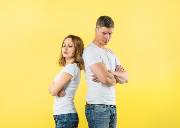 An angry young couple standing back o back against yellow background